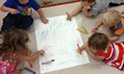 Five Children Coloring A Large Sheet of Paper