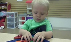 Young Boy Playing With Shapes Puzzle