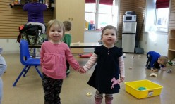 Two Young Girls Holding Hands and Smiling
