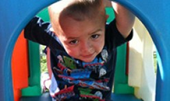 Young Boy Inside Outdoor Colorful Playhouse