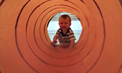 Young Boy Crawling Inside a Colorful Large Tube