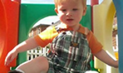 Young Boy Playing in Outdoor Colorful Playhouse
