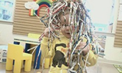 Child Covered in Fun Paper Strips
